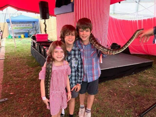 Three kids holding a snake at the Snake Boss show at Oktoberfest Brisbane