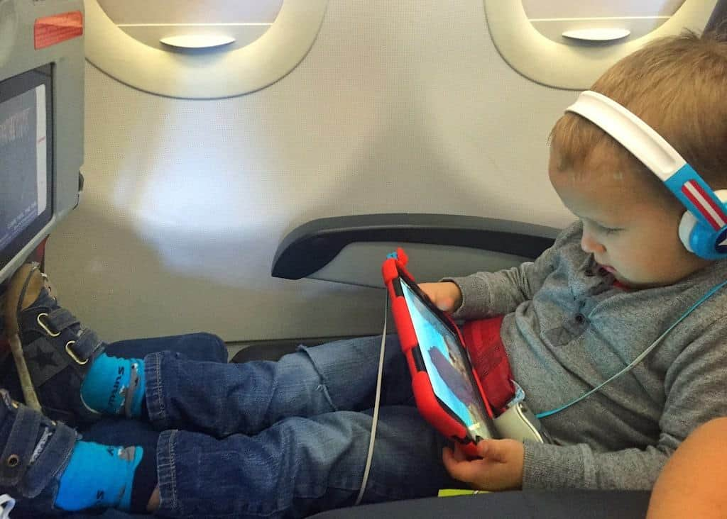 A child using 1st class kid pillow on a plane