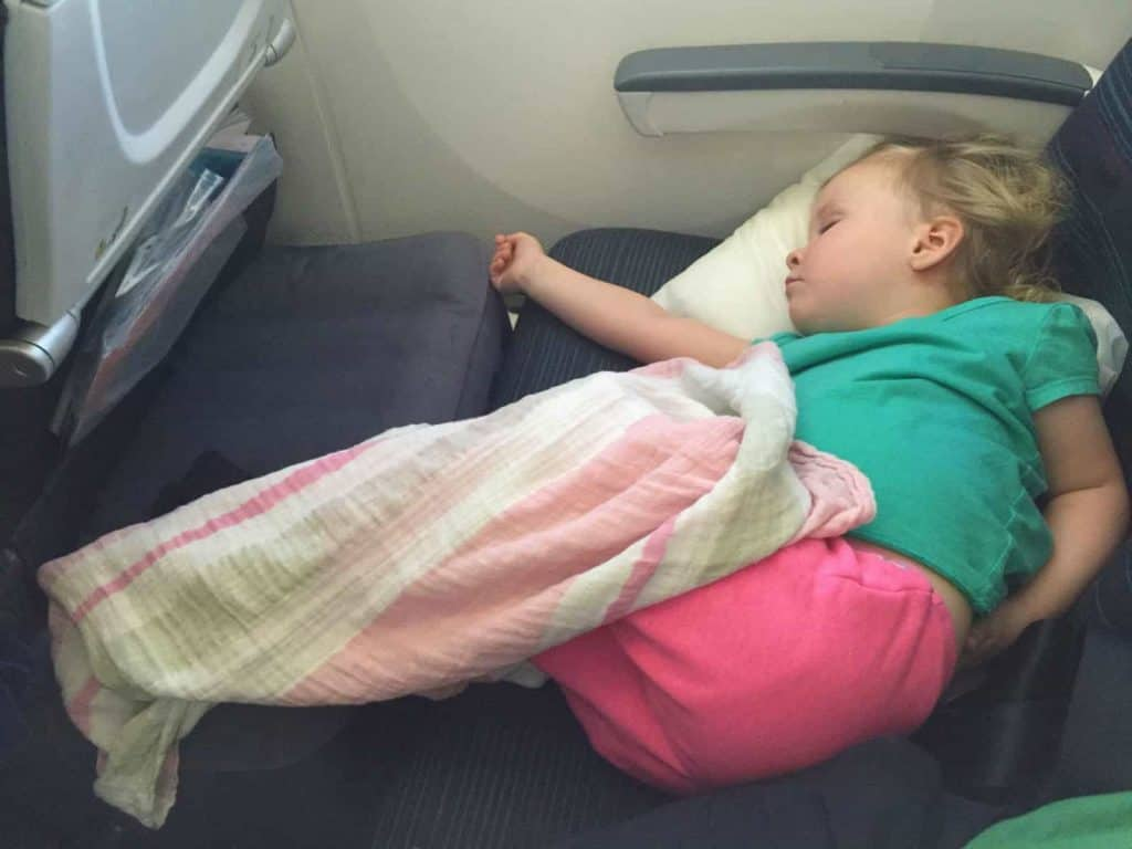 A child asleep on a Fly Tot kid' travel pillow on a plane