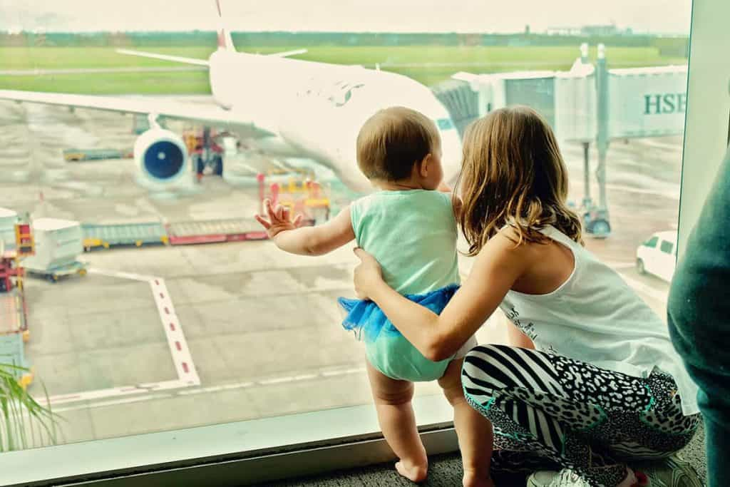 A baby and mother looking at a plane at the airport