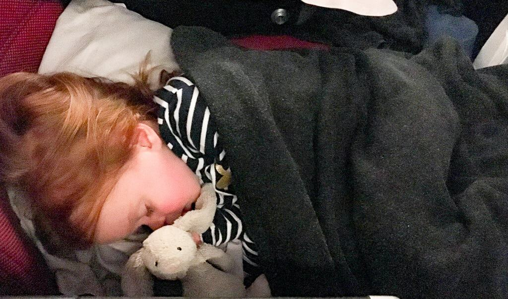 A child asleep on the 1st class kid travel pillow on a plane