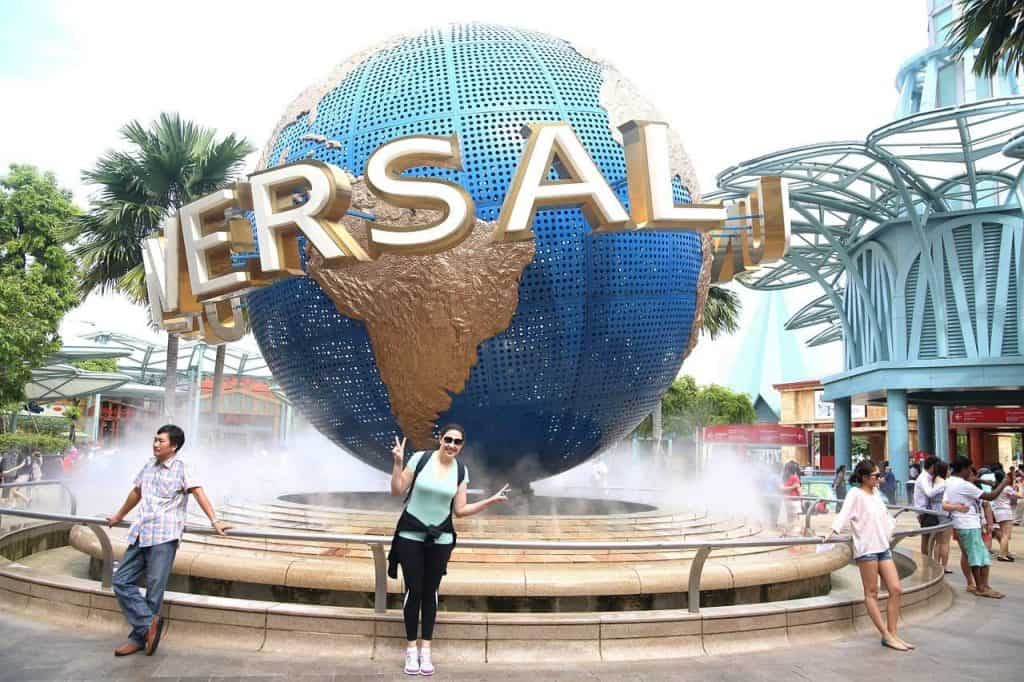 Someone standing in front of the Universal Studios Singapore globe water feature