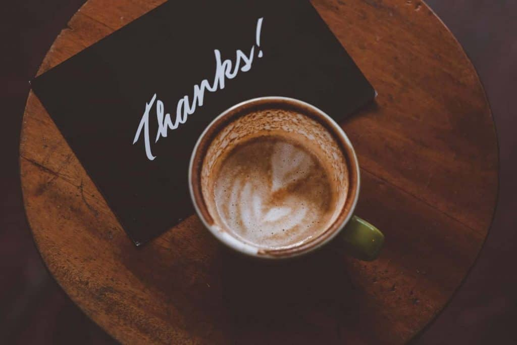 A card saying thanks by a coffee cup