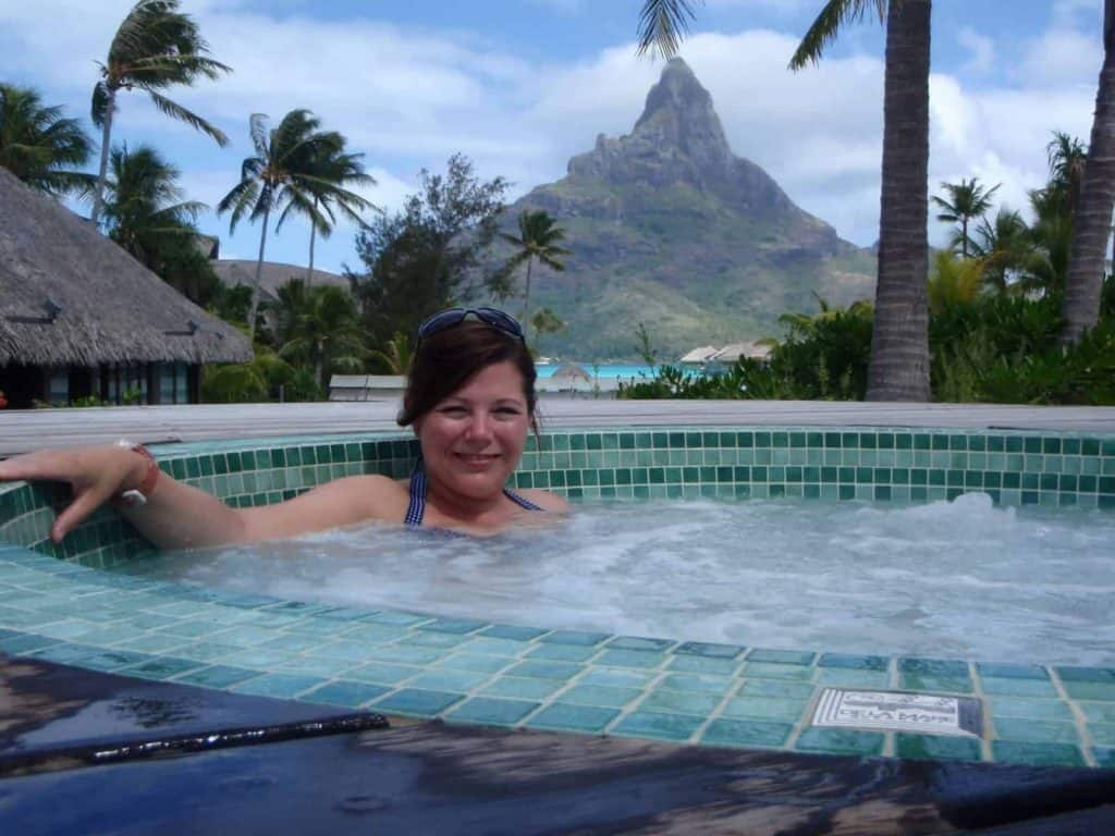 A girl in a jacuzzi in Bora Bora with a mountain backdrop