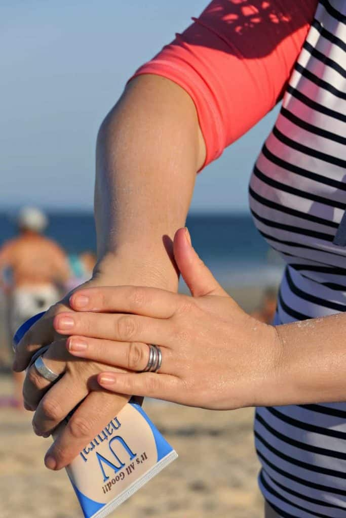 A woman applying zinc sunscreen to her arm on a beach