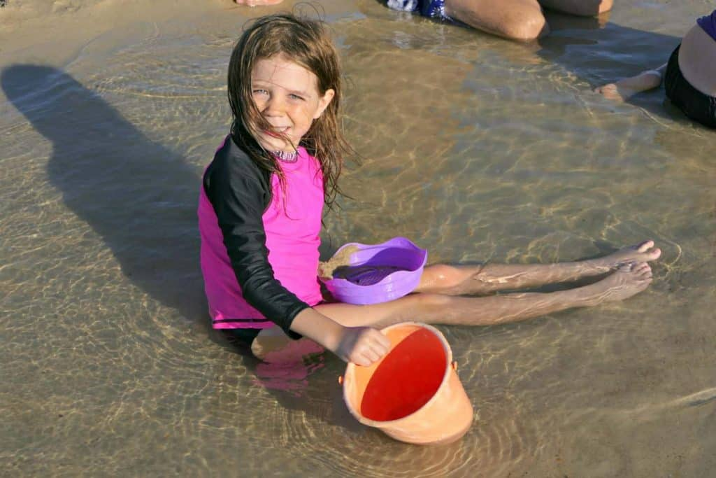 A girl on the beach with a bucket and spade wearing sunscreen