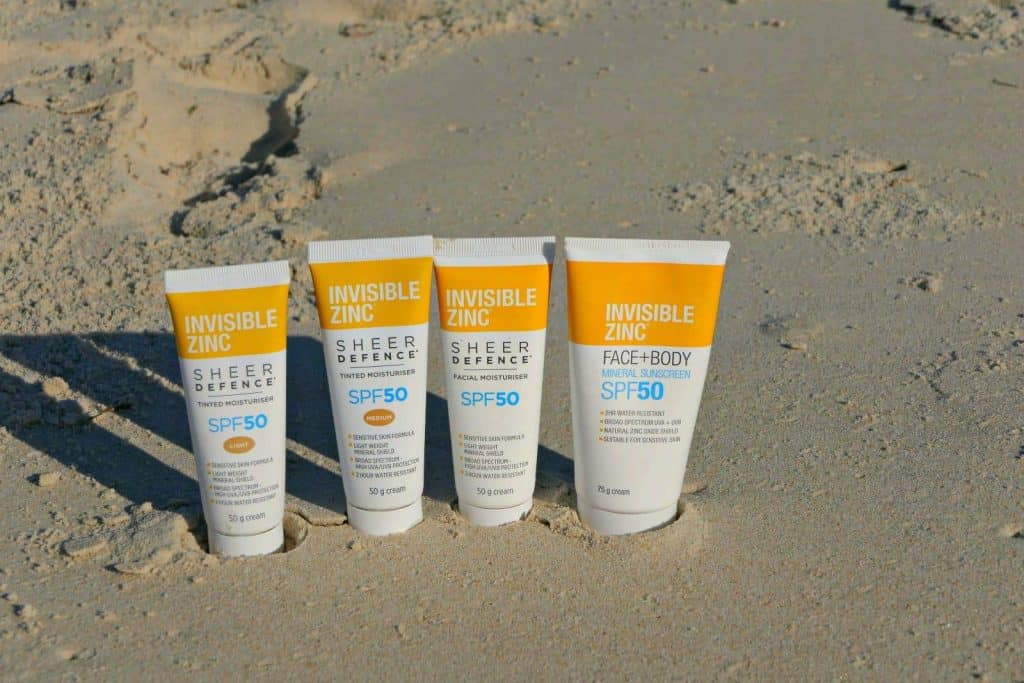 Bottles of Incredible Zinc sun cream in the sand on a beach
