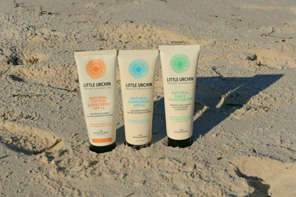 Bottles of Little Urchin natural zinc sunscreen for kids in the sand on a beach