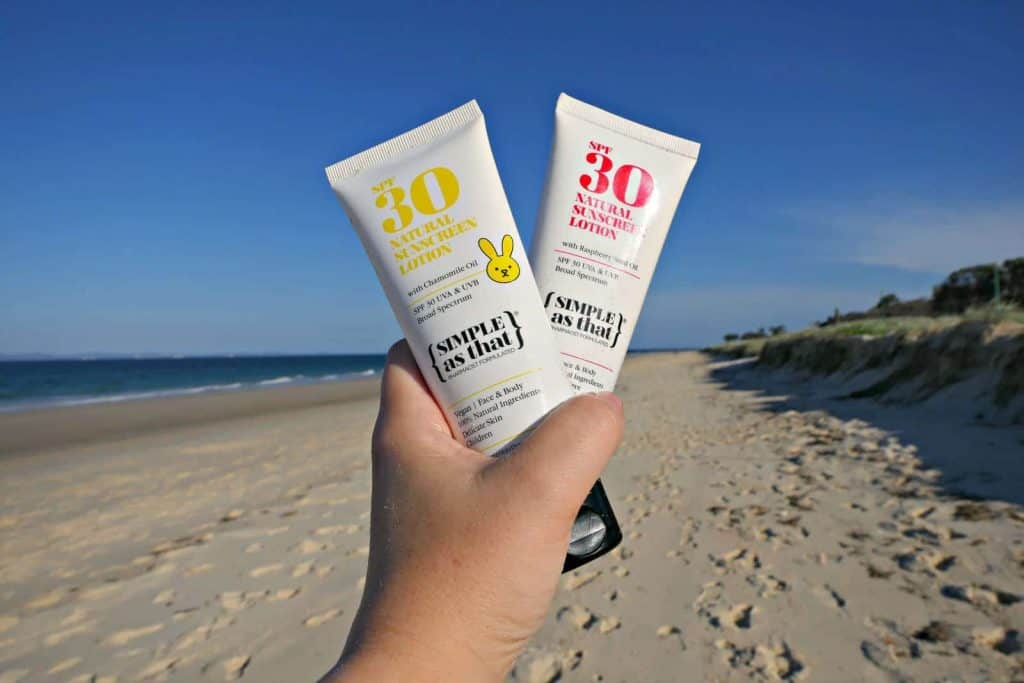 Bottles of Simple as that physical sunscreen being held over a beach