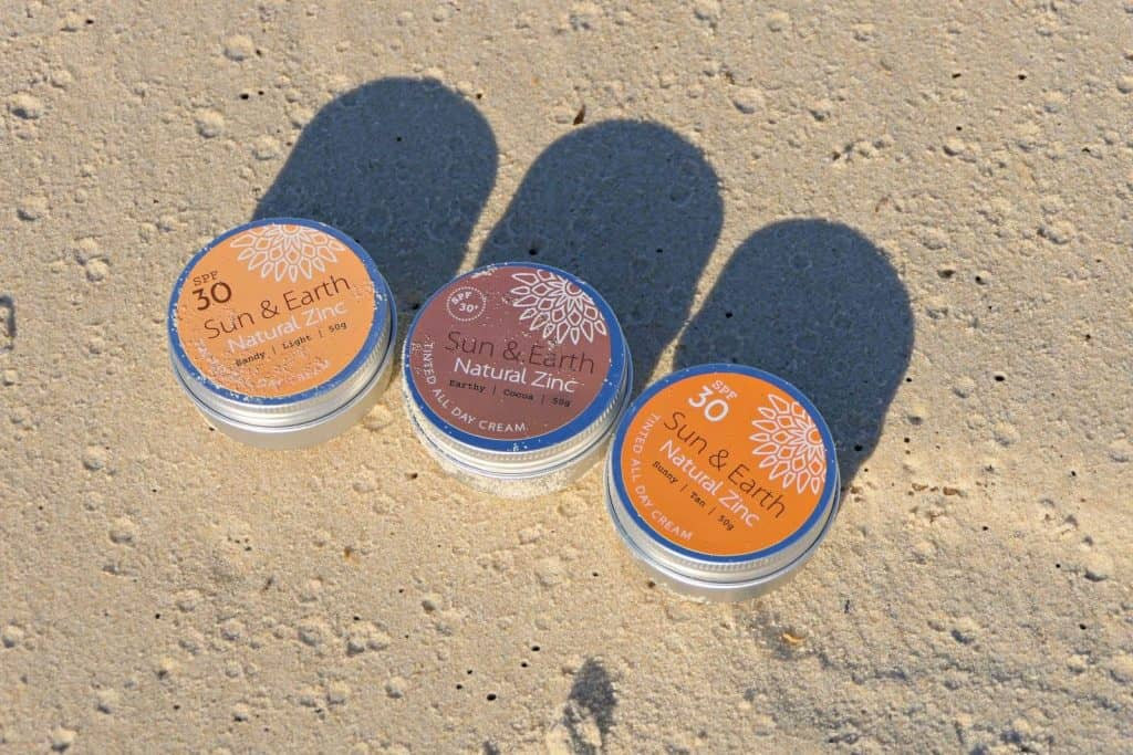 Pots of Sun and Earth zinc sunscreen in Australia on a beach