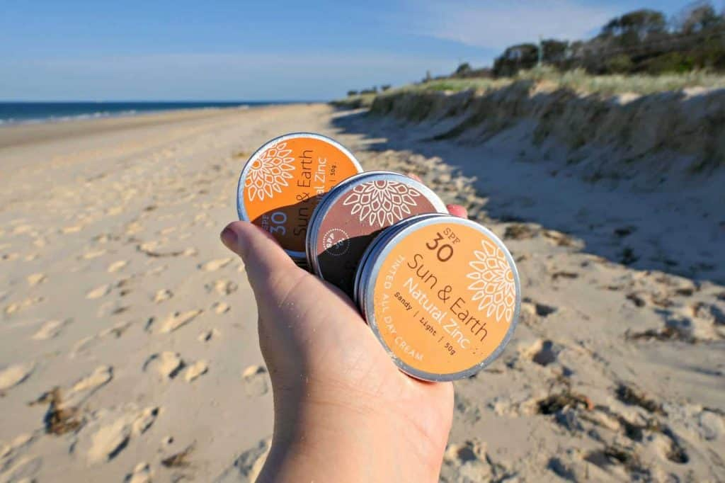 Tubs of Sun and Earth natural zinc sunscreen being held over a beach