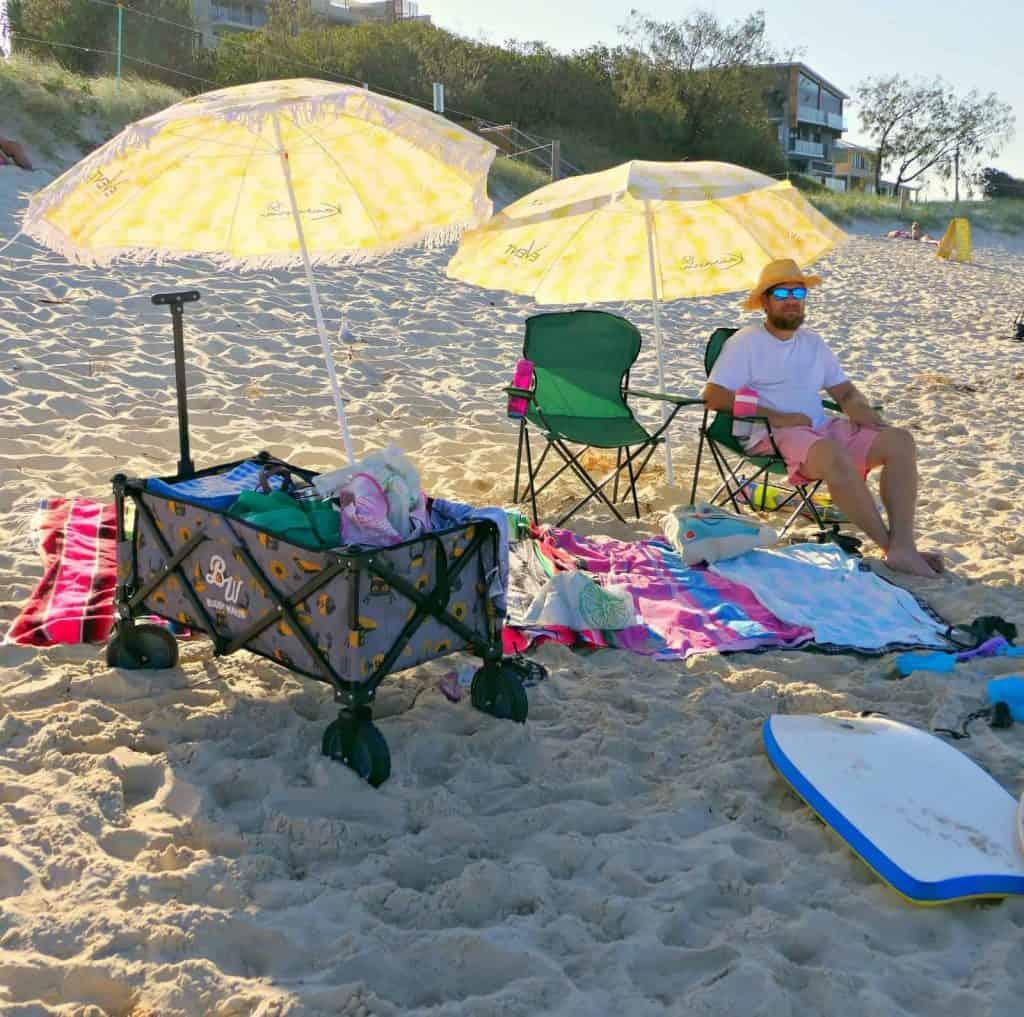 A man at the beach with a rug, umbrella and Buddy Wagon beach cart