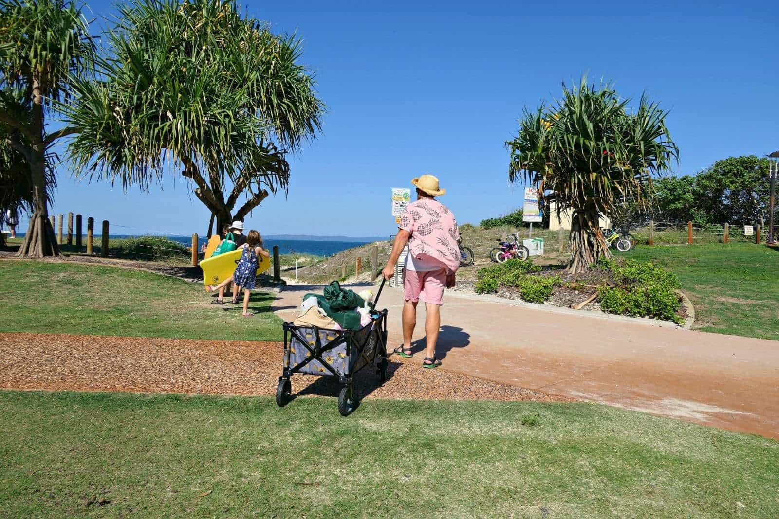 A man pulling a Buddy Wagon beach cart