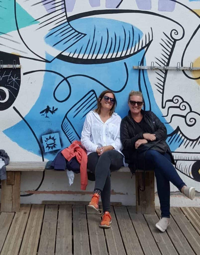 Danni and Jen, Founders of Buddy Wagon sitting on a bench