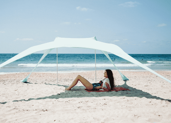 A white beach shade on the sand with a girl under it
