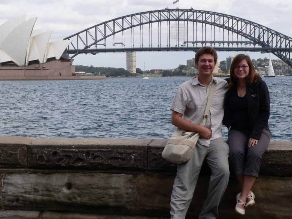 A couple sitting on a wall in Sydney Harbour