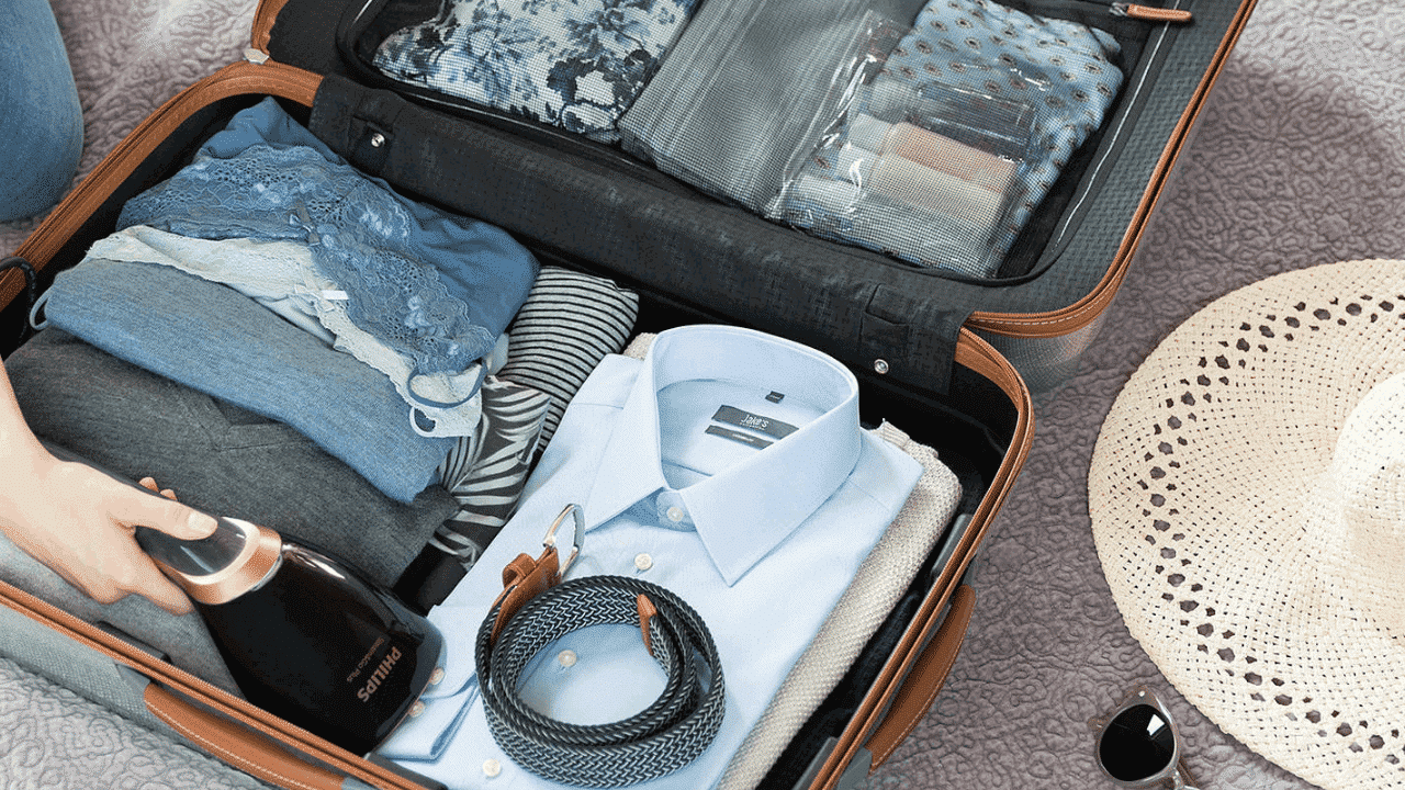A suitcase full of travel accessories and travel gadgets including a Philips garment steamer