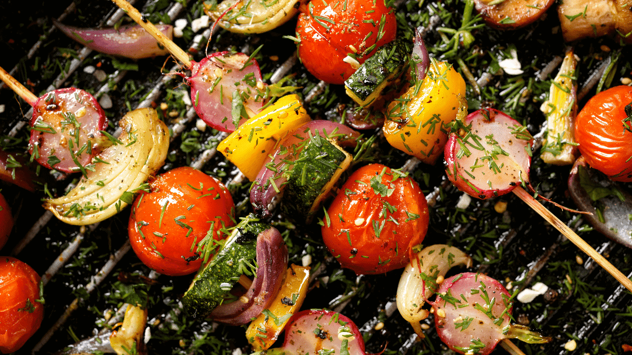 Vegetable kebabs cooking on a bbq