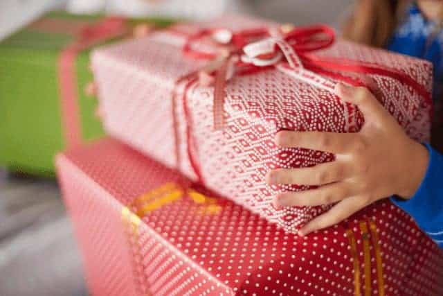 A child holding moving to Australia leaving gifts wrapped in red paper