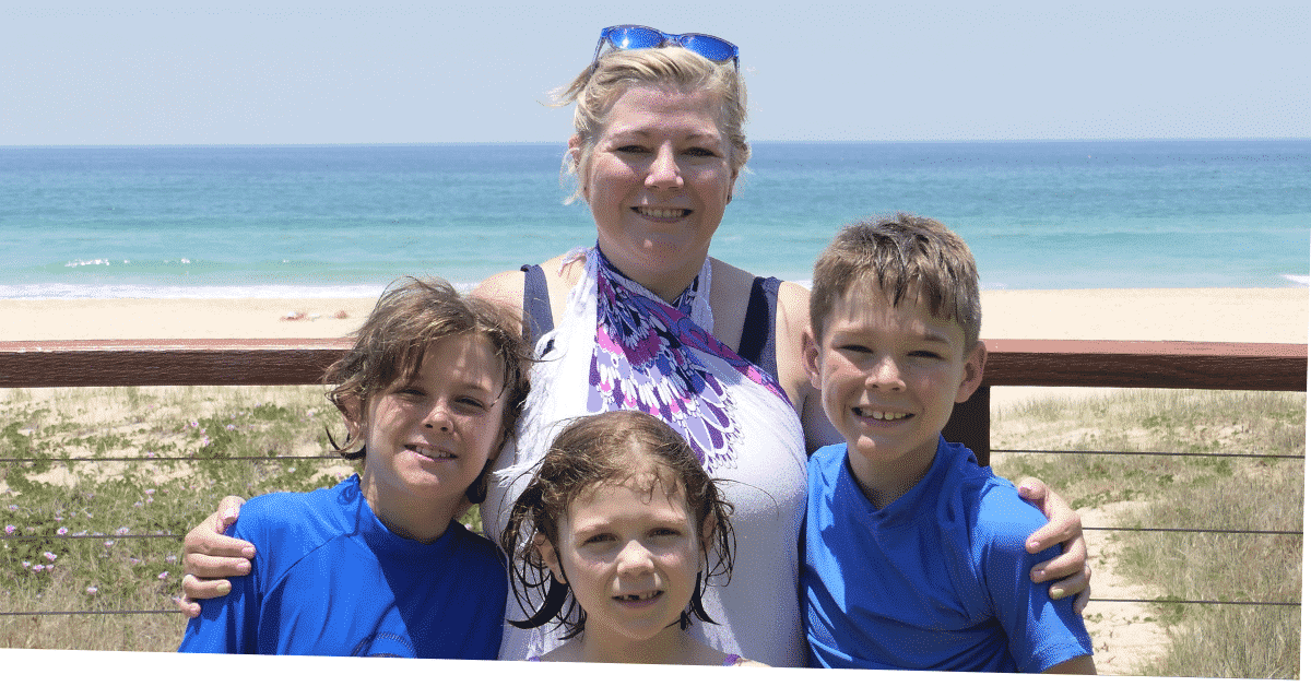 A mum and three kids by the beach