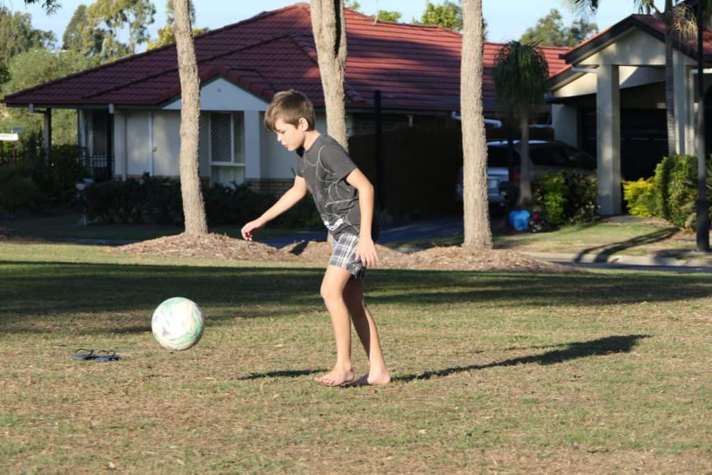 A boy playing soccer at the park