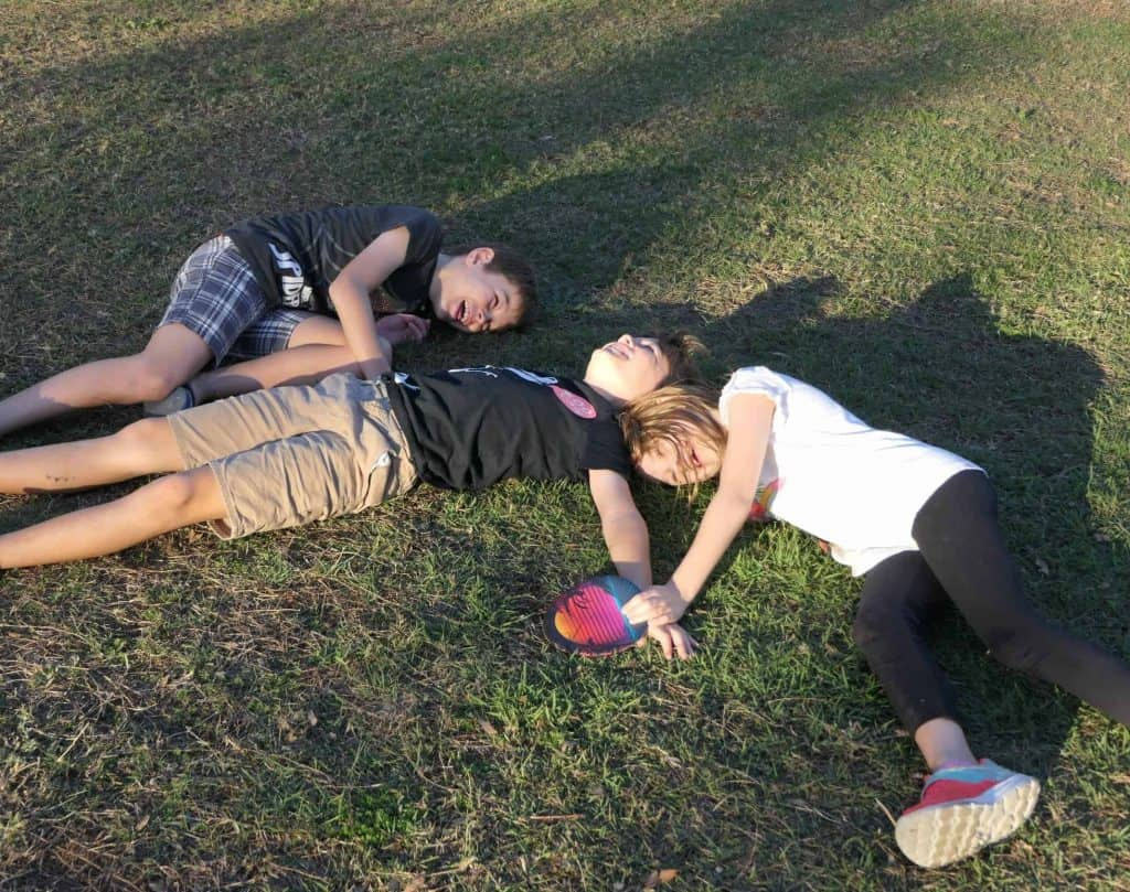Three kids laying on the grass