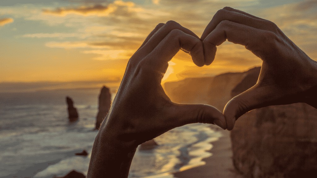 A hand making a heart shape to capture the sunset in Australia