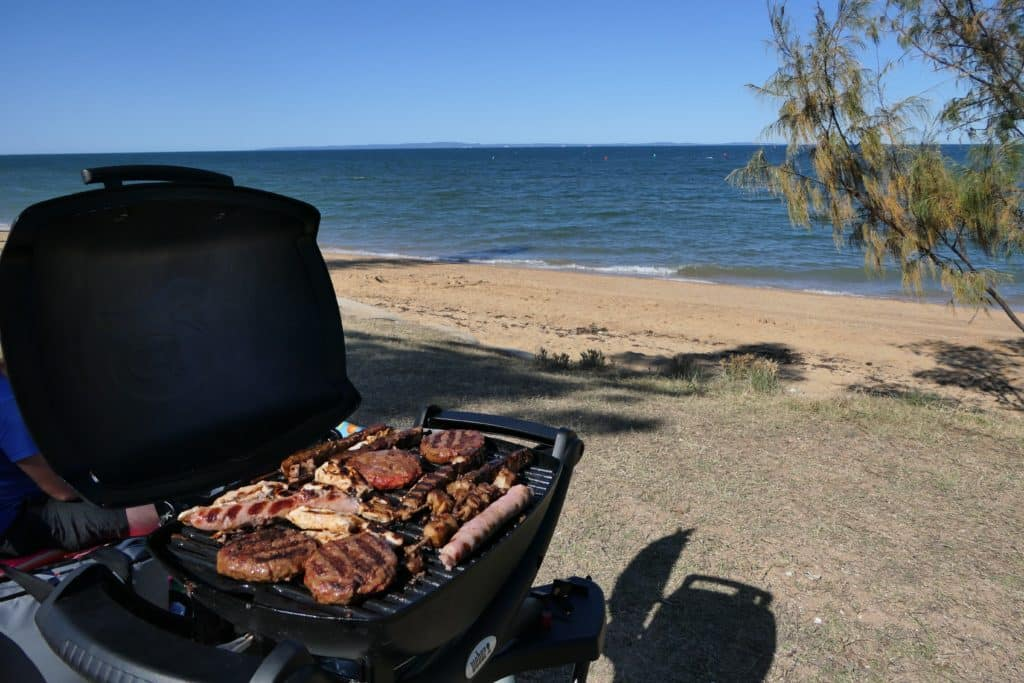 A Weber Baby Q1000 BBQ with food on the grill set up beside the beach