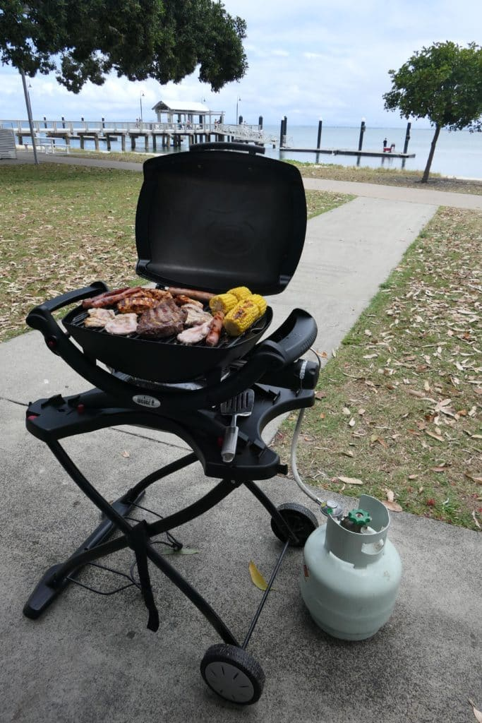 A Weber Baby Q trolley and BBQ cooking food by the beach